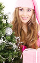 Santa helper girl with gift box and christmas tree Royalty Free Stock Photos
