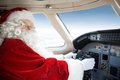 Santa holding control wheel in cockpit of private portrait man costume jet Stock Images