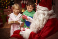 Santa with kids this is for you and this for your little sister Royalty Free Stock Images