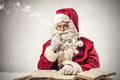 Santa klaus smoking a pipe and reading Royalty Free Stock Photo