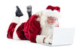 Santa lies in front of his laptop on white background Stock Images