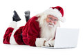 Santa lies in front of his laptop on white background Stock Photos