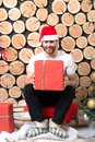Santa man with box sit on wood log background Royalty Free Stock Photo