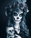 Santa muerte young woman with artistic visage and with roses in her hair Royalty Free Stock Images