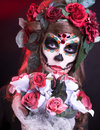 Santa muerte young woman with artistic visage and with roses in her hair Stock Image
