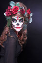 Santa muerte young woman with artistic visage and with roses in her hair Stock Images