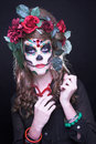Santa muerte young woman with artistic visage and with roses in her hair Royalty Free Stock Image