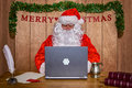 Santa online sat at his desk in the north pole doing some christmas shopping and answering his emails Royalty Free Stock Images
