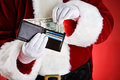 Santa pulling cash out of wallet anonymous claus on a red background holding various props gifts etc Stock Photo
