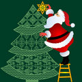 Santa putting topper on tree Royalty Free Stock Photo