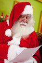 Santa reading a Christmas letter Royalty Free Stock Photography