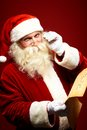 Santa reading letter portrait of happy claus holding christmas and looking at camera Stock Photos