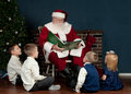 Santa reading to kids a christmas book in a home with a fireplace hung with stockings and christmas tree a group of young boys and Stock Photo