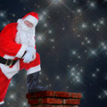 Santa resting foot on chimney claus standing a roof with one the his arms are folded and he is leaning his knee against a starry Stock Photos
