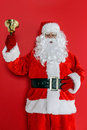 Santa ringing his bell claus or father christmas against a red background Royalty Free Stock Photo
