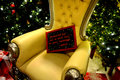 Santa s chair with a chalkboard sign that says reindeer got out of their pen be back tomorrow Stock Photo