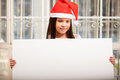 Santa s girl holding a sign happy little wearing hat and big at home Royalty Free Stock Photos