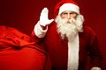 Santa and sack portrait of claus raising his hand with huge red near by Royalty Free Stock Image