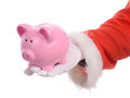 Santa savings sant handing out a coin piggy bank concept of christmas isolated on a white background Stock Photo