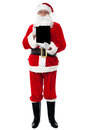 Santa showing newly launched tablet pc Royalty Free Stock Photo