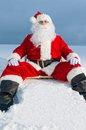 Santa sitting on sunbed in snow Stock Photo