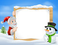 Santa snowman cartoon sign and with cute and characters in a winter snow scene Stock Photo