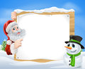 Santa snowman snow scene and cartoon with and a cartoon in a winter framing a wooden sign Royalty Free Stock Image
