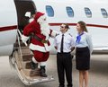 Santa thanking pilot and airhostess while disembarking private jet at airport terminal Stock Photography