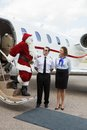 Santa travelling on private jet thanking pilot and airhostess while standing ladder of Royalty Free Stock Images
