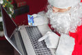 Santa using laptop computer, buying by plastic card Christmas gift Royalty Free Stock Photo