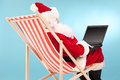 Santa working on laptop seated in a sun lounger claus blue background rear view Royalty Free Stock Image