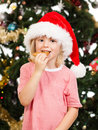 Santas helper eating gingerbread cute boy dressed as santa s is a cookie in front of a christmas tree Royalty Free Stock Photo