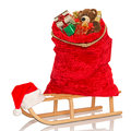 Santas sack on sledge isolated full of gift wrapped christmas presents and toys a wooden a white background Stock Images
