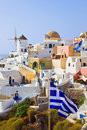 Santorini view (Oia) and greek flag Royalty Free Stock Photography