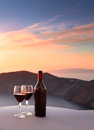 Santorini wine bottle and glasses overlooking cliffs Stock Images