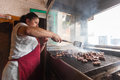 Sarajevo bosnia and herzegovina aug woman grills cevapi on august in b h cevap is a bosnian traditional meat grilled dish Stock Images