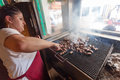 Sarajevo bosnia and herzegovina aug woman grills cevapi on august in b h cevap is a bosnian traditional meat grilled dish Stock Photos