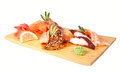 Sashimi set isolated on white with perch rudderfish tuna squid octopus shrimps and eel wooden board with wasabi and lemon Stock Photo