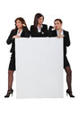 Sassy businesswomen with a board left blank for your message Royalty Free Stock Images