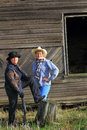 Sassy gunslinger cowgirls two older cowboy ladies wearing hats holding a rifle standing by an old barn wood wall copy space Stock Image