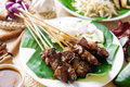 Satay or sate skewered and grilled meat served with peanut sauce cucumber and ketupat malaysia or indonesia food traditional malay Royalty Free Stock Photo