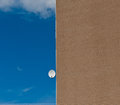Satellite antenna on the house wall against the blue sky on a sunny day Stock Photo