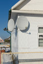Satellite antenna two dishes to receive television transmissions installed on the wall Stock Photos