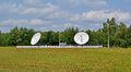 Satellite antennas green trees and thunderstorm blue sky few large Stock Photography