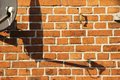 Satellite dish casts shadow a on a brick building a Stock Photography