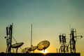 Satellite dish and communication tower silhouette on sunset time Stock Photos