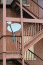 Satellite dish on fire escape a television mounted stairs next to brick building Stock Photo