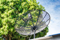 Satellite dish on the roof with blue sky and tree. Royalty Free Stock Photo