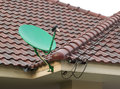 Satellite dish on the roof of tile green Stock Photos