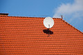 Satellite dish tv on red tiles roof Stock Image